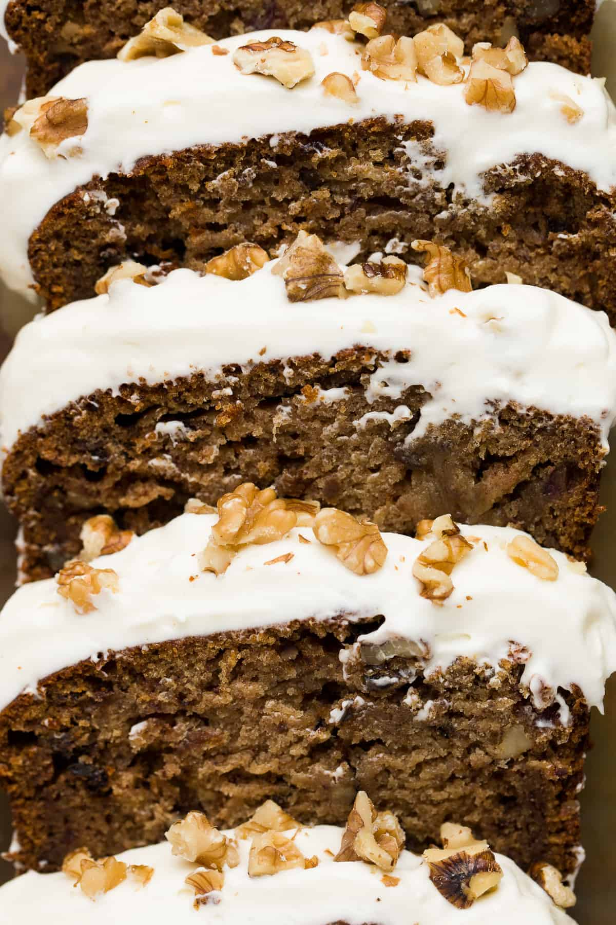 A close up image of a loaf cake that has been cut into slices. There are visible chopped walnuts and dates and a thick layer of white coloured frosting.