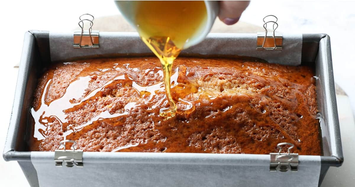 Drizzling golden syrup on top of a baked cake.