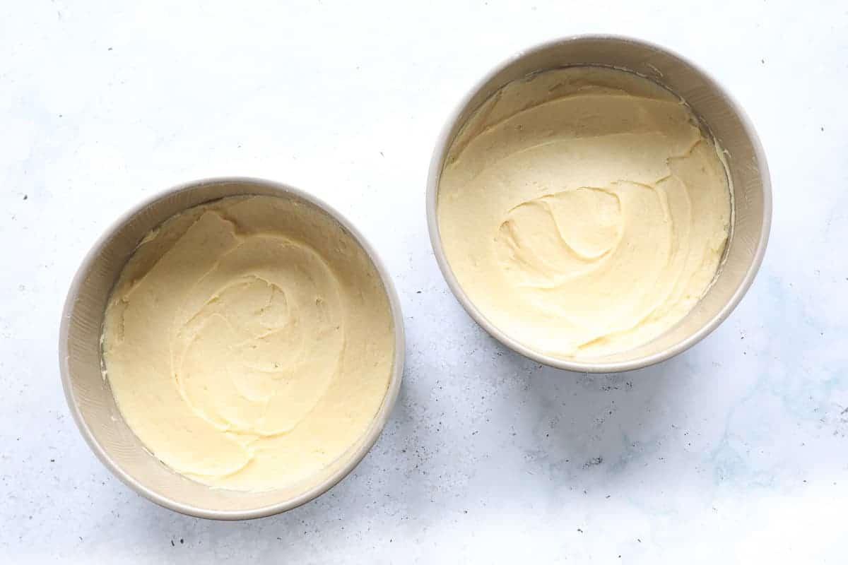 Two 8 inch (20 cm) cake tins containing cake mixture.