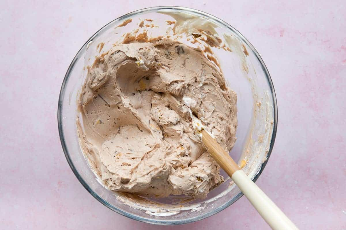 Double cream has been whipped to stiff peaks and added to a chocolate cheesecake mixture in a glass bowl.