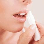 Woman applying homemade lip balm on her lips