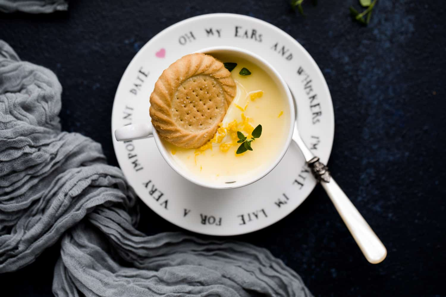 A lemon posset dessert in a teacup with a shortbread biscuit balanced on top