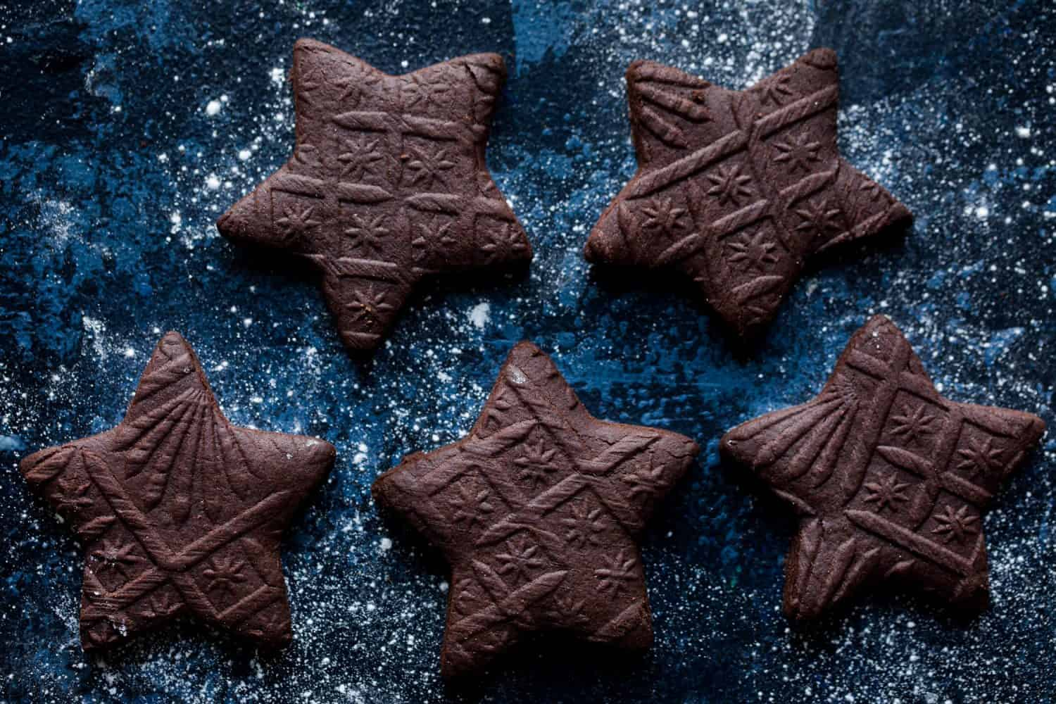 5 star shaped biscuits on a dark blue background that have been rolled with a pattern rolling pin.