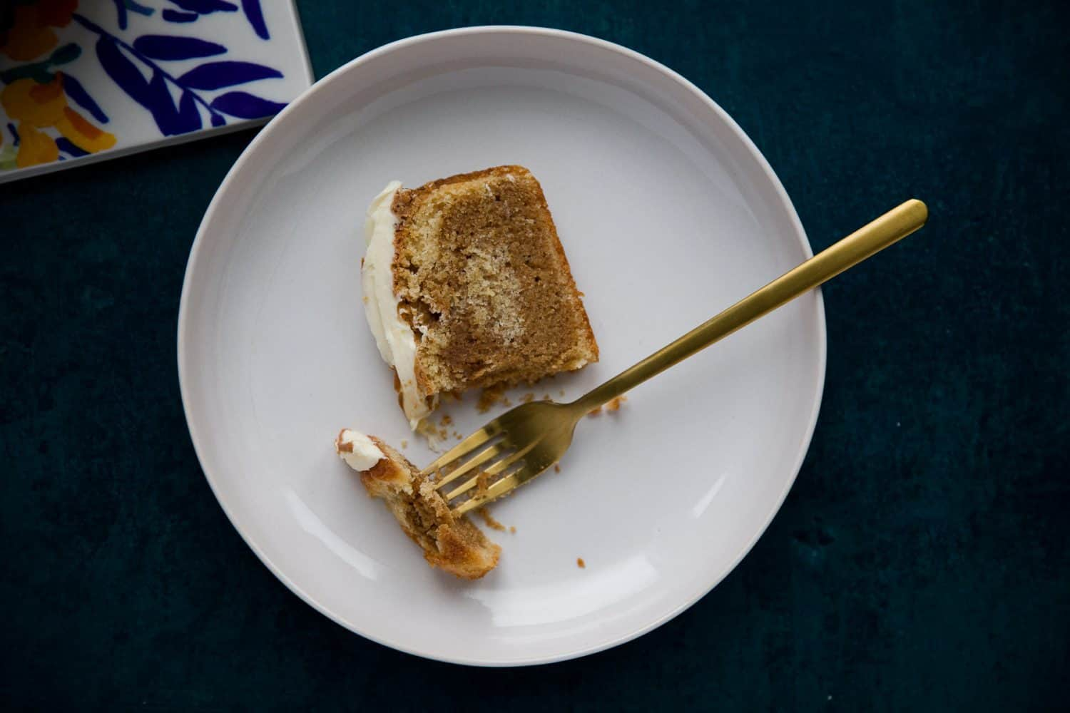 A slice of Biscoff Cake on a white plate with a gold fork.