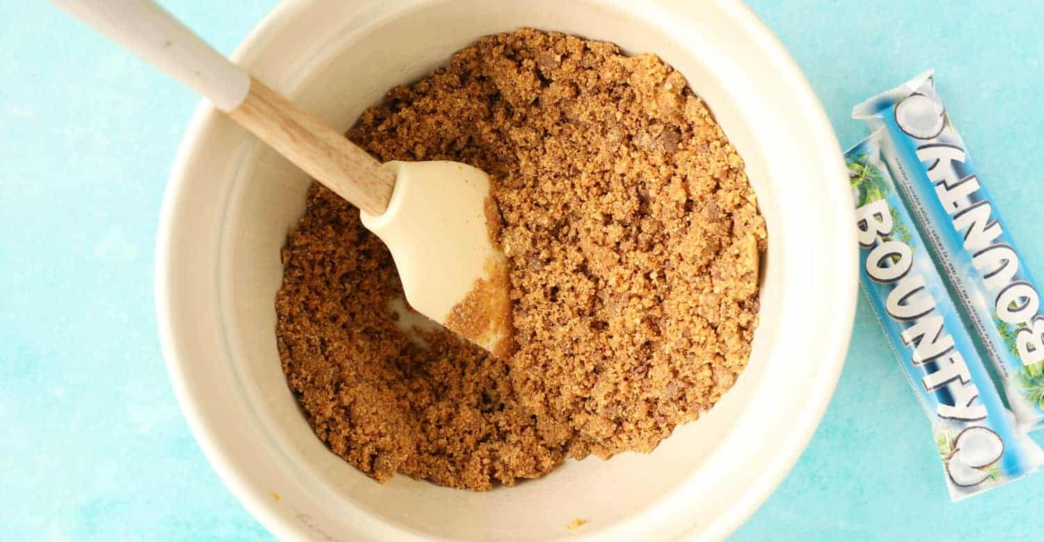 A bowl of digestive crumbs with melted butter mixed in to form the base of a Bounty Cheesecake