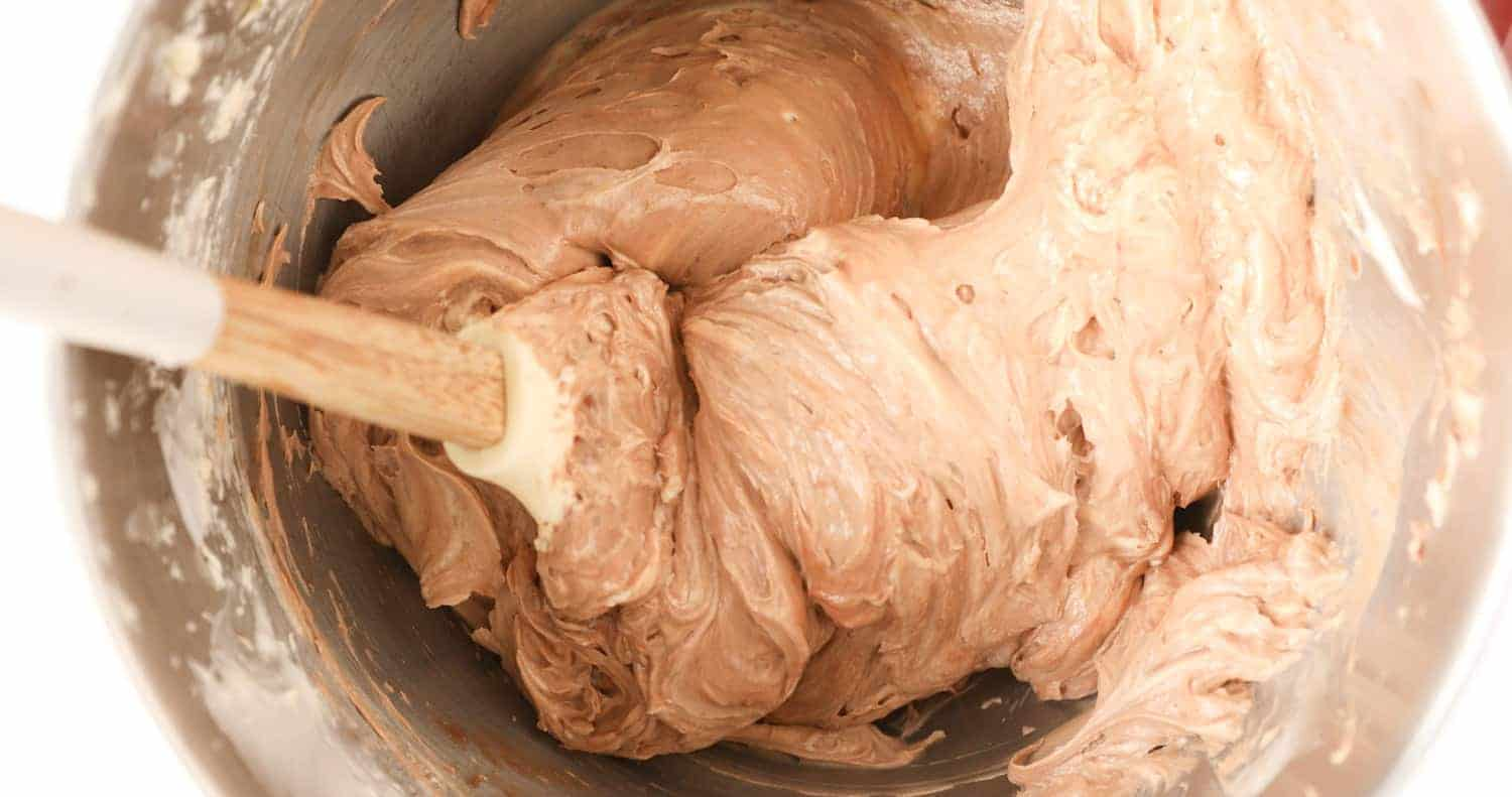A bowl of buttercream that has had nutella mixed in.