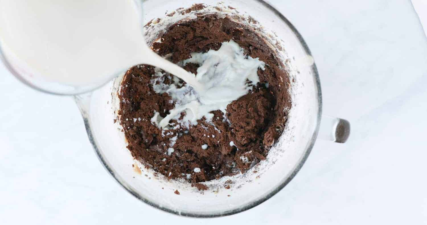 Pouring milk into a chocolate cake mixture