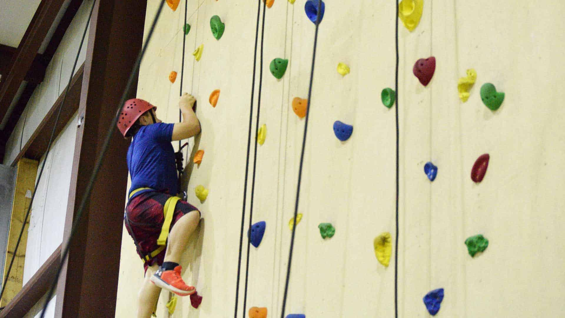 Teenage boy climbing a rock wall