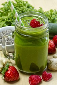 healthy green juice surrounded by fruit and vegetables