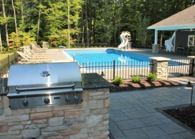 Grill view of pool, slide, pool house, fence and landscaping.