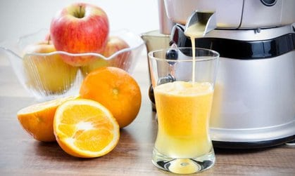 How to use a juicer with orange juice dripping from juicer into glass and cut orange and whole apples