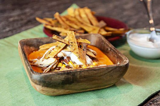 chicken enchilada soup in a wooden bowl on a green placemat