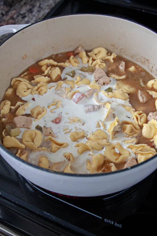 cheese tortellini and vegetables in chicken broth and cream in dutch oven