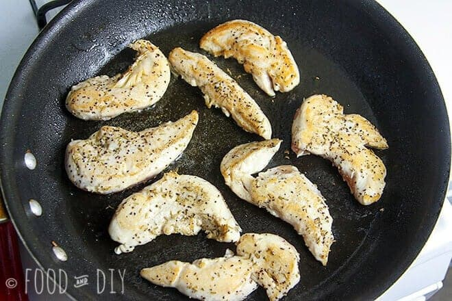 Chicken tenders cooking in olive oil in a skillet