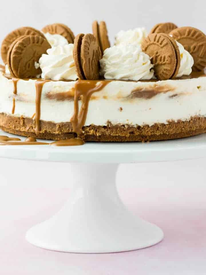 A cheesecake drizzled with biscoff spread and topped with cream and biscuits on a white cake stand.