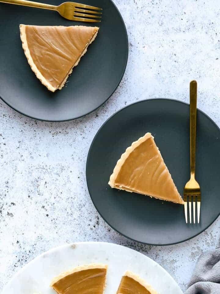 Slices of butterscotch tart o dark grey serving plates.