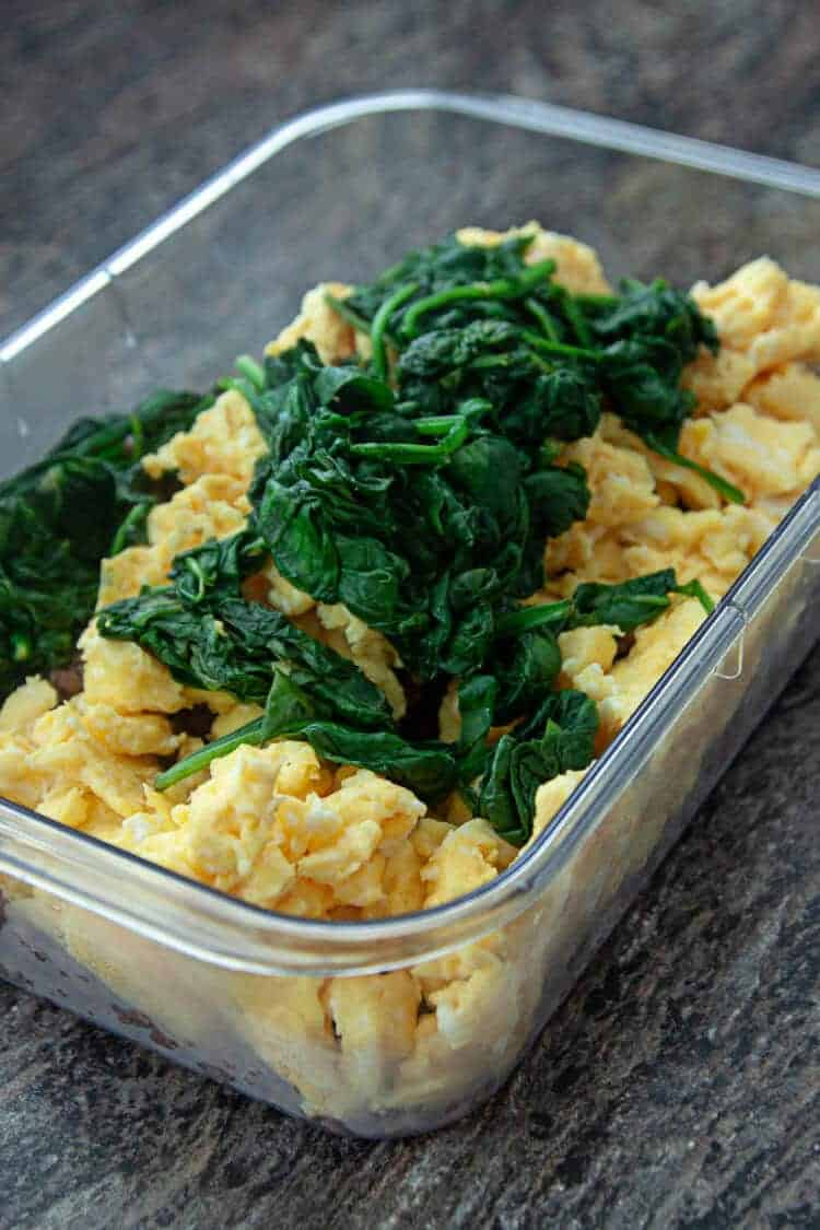 browned sausage, scrambled eggs, wilted spinach in plastic storage container