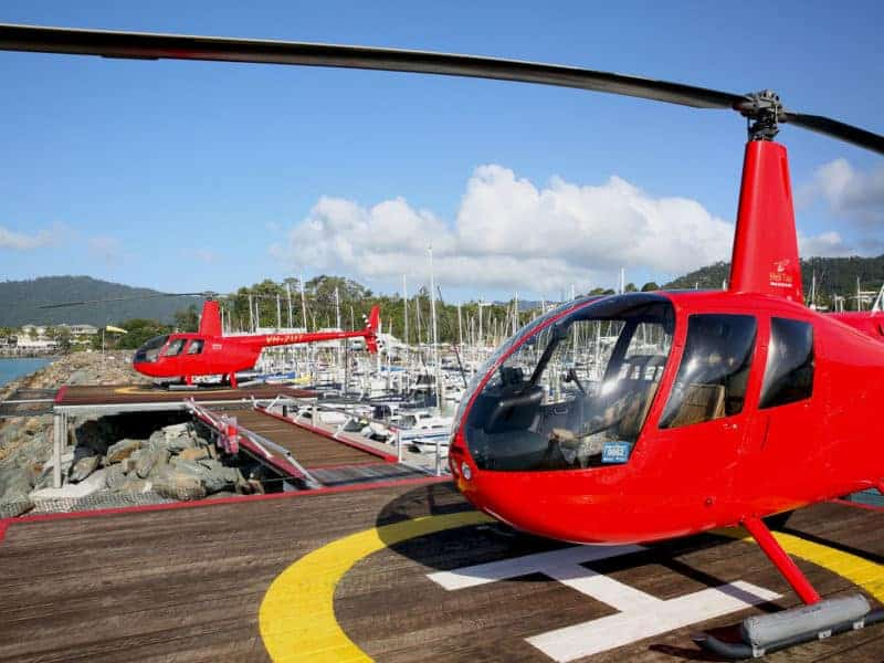 Private helicopter pads at Coral Sea Marina with two helicopters landed and ready for departure