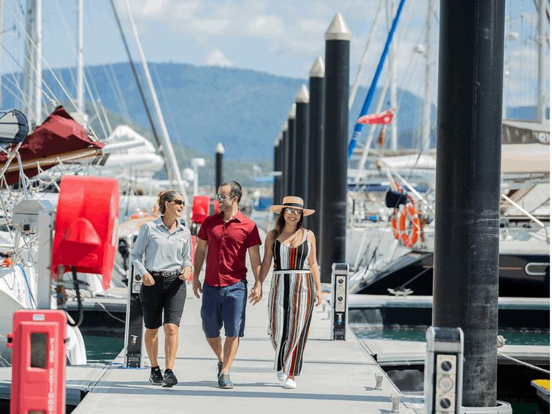 A dockhand showing marina guests through Coral Sea Marina