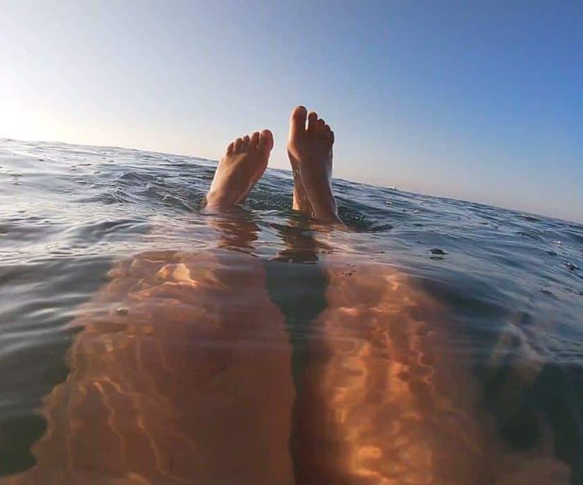 Gemma's feet sticking out of the sea on a sea swim