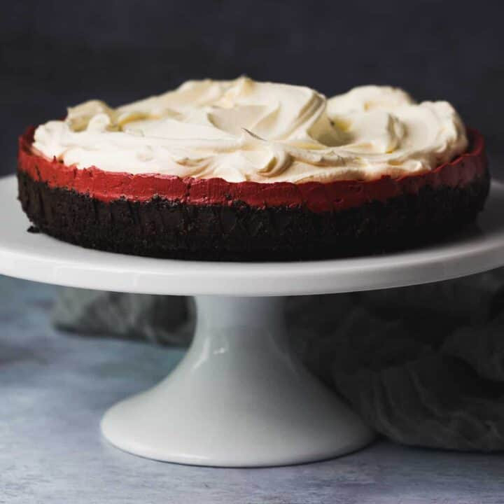 A red velvet cheesecake on a white cake stand